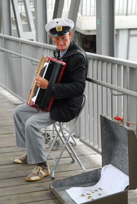 53- Hamburg ein Seemann mit Akkordeon macht Straßenmusik.