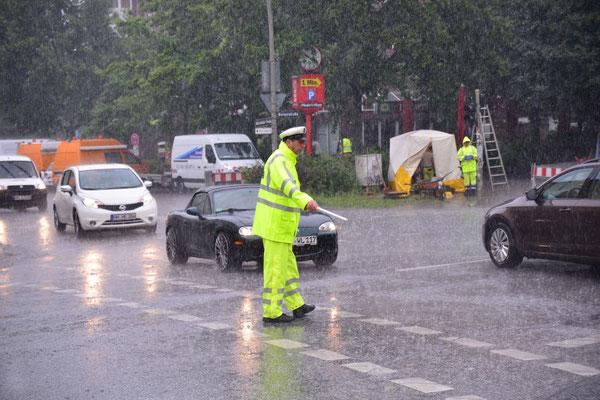 27- Polizist regelt straßenverkehr, Regen