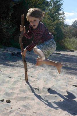 16- Junge springt am Strand