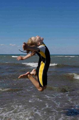 18 - Junge springt ausgelassen am Strand im Neoprenanzug