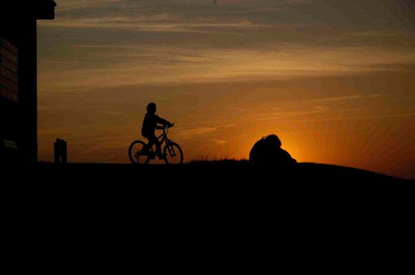 15- Junge auf dem Fahrrad bei Sonnenuntergang