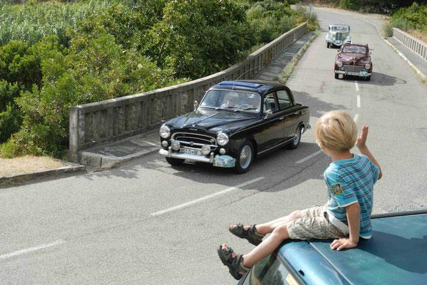leiner Junge winkt Oldtimern bei einer Rallye vom Strassenrand zu