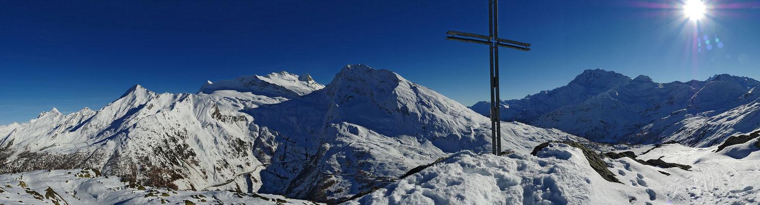 Der Blick vom Gipfel steht seinen grösseren Nachbarn in nichts nach. Links vom Kreuz Bortelhorn, Wasenhorn, Monte Leone, Breithorn und Hübschhorn, rechts davon Fletschhorn und Senggchuppa