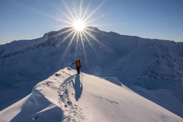 Die Sonne steht im Februar noch tief am Nachmittagshimmel und zaubert ein spezielles warmes Licht auf den Gipfelgrat