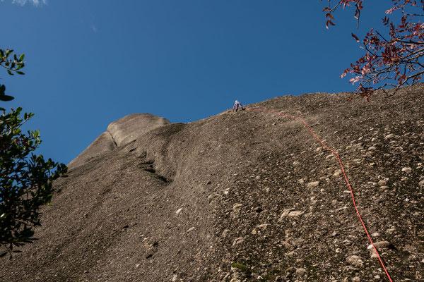 Franziska im ungewohnten Felsenmeer von tausenden Kieseln. Die Absicherung ist spärlich und die Morgenfeuchte mit dem vermoosten Fels nur etwas für ein intaktes Nervenkostüm