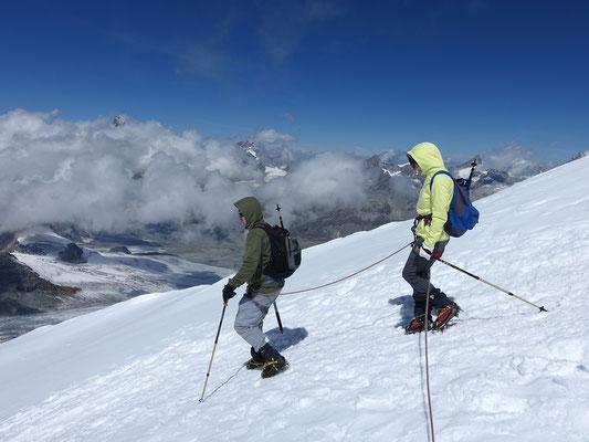 Hans Ueli und Liana auf dem Abstieg, dabei ragen Matterhorn, Dent Blanche, Obergabelhorn, Zinalrothorn und Weisshorn aus den Wolken heraus