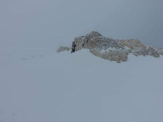 Am Fuss des Gipfelhanges bekommen wir ausser den charakteristischen weissen Felsen nichts zu Gesicht. Auch der Föhn hat an Stärke zugenommen. So entschliessen wir uns, sogleich die Abfahrt Richtung Fextal anzugehen. Der Piz Bernina muss warten...