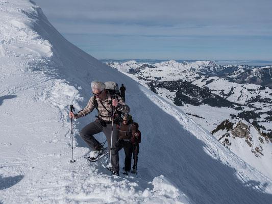 Am Ausstieg zum breiten Gipfelgrat strählt der Föhn unsere Haare ins Lee der Nordflanke