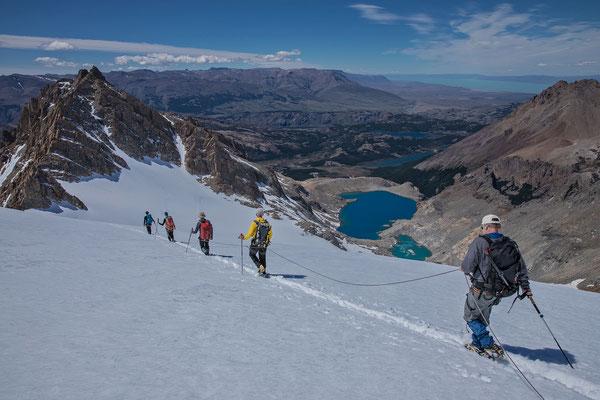 Bestens gelaunt machen wir uns an den Abstieg. Links der Cerro Madsen, unter uns die Laguna de los Tres, die langgezogene Laguna Madre, dahinter die Laguna Capri und in weiter Ferne der Lago Viedma
