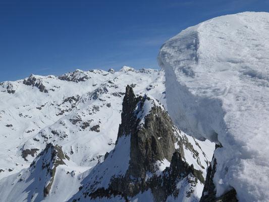 Blick vom Gross Schinhorn Richtung Binntal. Die Binntalhütte wird von der spitzen Felsnadel des Klein Schinhorn verdeckt. In der Bildmitte am Horizont das Hohsandhorn