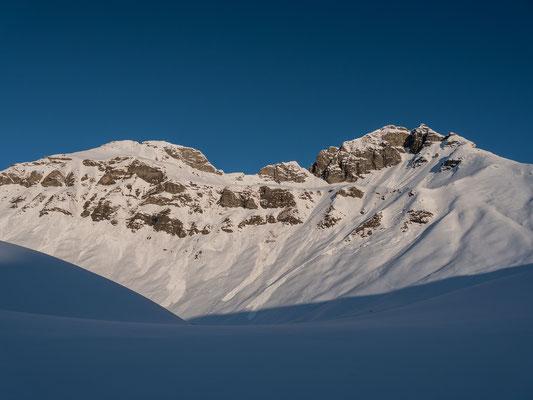 Endlich geht die Sonne auf. Blick von der Alp Ottere zum Winterhore und zum Erbithore links. Der Aufstieg erfolgt über die versteckte Rampe und den steilen Schlusshang zur wenig ausgeprägten Scharte