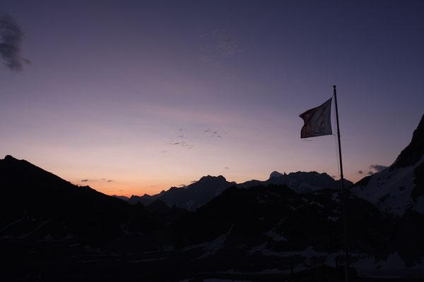 Morgenstund vor der Cab. des Dix. Gleich links unterhalb der flatternden Fahne ragt die markande Nadel der Aiguille de la Tsa in den golden gefärbten Himmel, links anschliessend die Dent Blanche