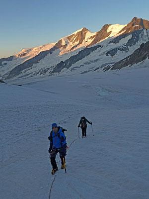 Am Rand eines alten Eislawinenzuges steigen wir Richtung Fieschergrat. Dahinter leuchtet die Wannenhorn Gruppe in der Morgensonne