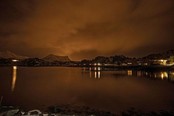Nordlichter waren an unserem ersten Abend keine zu sehen, aber die weit verstreuten Lichtquellen zauberten trotzdem ihr Licht in den bewölkten Nachthimmel. Rechts im Bild unsere Unterkunft in Orsvagvaer