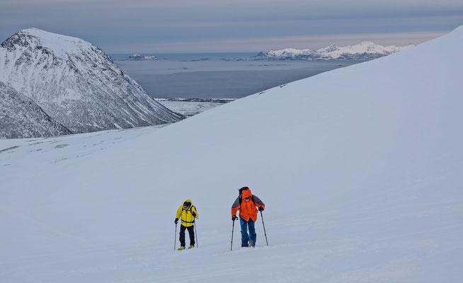 Die Schneeschuhläufer schwenken vorher rechts weg und besteigen mit Meerblick den Sautinden