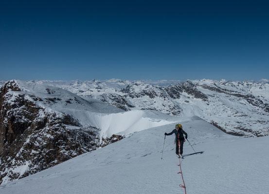 Welch ein Horizont, da reiht sich Gipfel an Gipfel. Angeseilt sind wir durch die Spaltenzonen des Vadret da la Sella aufgestiegen und an der glashart gefrorenen Gipfelkuppe kommen auch noch die Harsteisen zum Einsatz