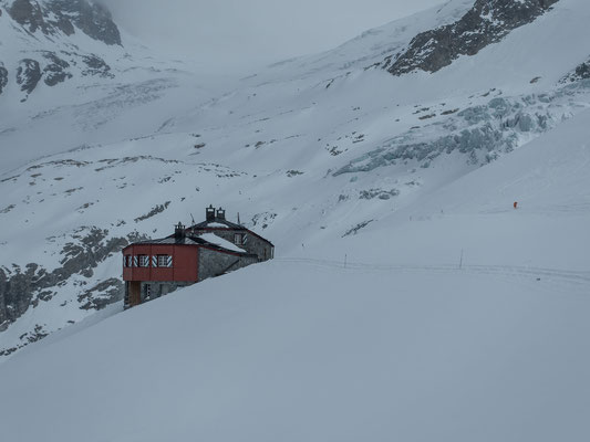 Nach ein paar abwechslungsreichen Metern mit Fixseilen, Powderhängen und kurzem Aufstieg erreichen Klaus und ich die prächtig gelegene Coaz Hütte
