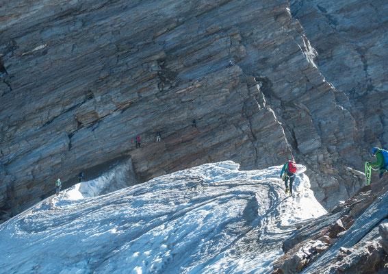 Gleich 8 Bergsteiger einer Gruppe tun sich schwer beim Klettern mit Steigeisen