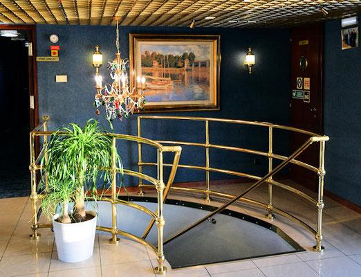Espace réception - escalier de communication pont supérieur pont principal - A la cloison une reproduction du peintre Claude Monet : Le pont d'Argenteuil