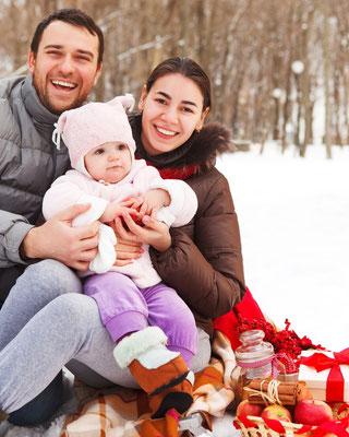 Kleine Familie mit Baby bei Picknick im Schnee