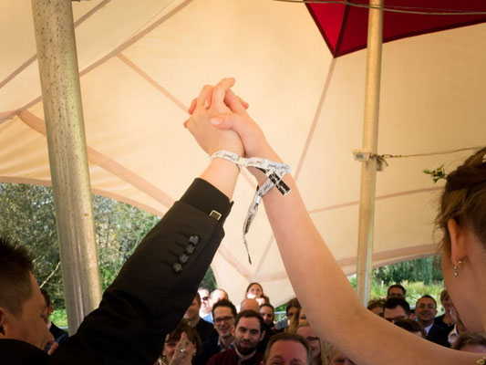 """Brautpaar mit Just-Married-Festival-Bändern am Handgelenk bei freier Trauung """"Heart-Rock-Festival"""" – Foto von Henning Fösser"""