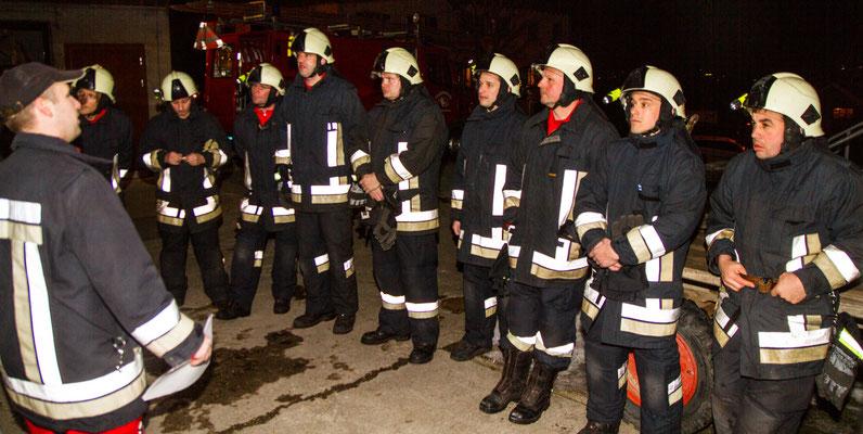 Eine Gruppe Feuerwehrleute werden übungshalber auf für einen Absucheinsatz instruiert.