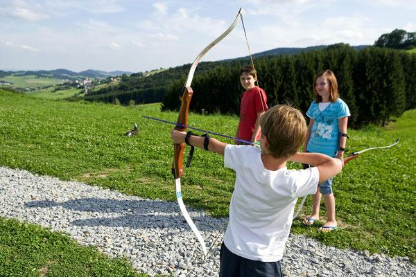 Ein Kind zielt mit dem Bogen auf eine Zielscheibe