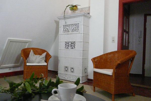 Antiker weißer Kachelofen voll funktionstüchtig und Sitzgruppe mit Korbsessel