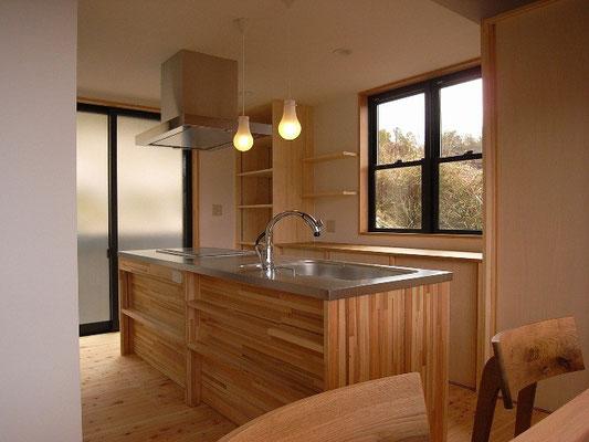 アイランド型キッチン。後ろの上げ下げ窓の外にはプランター(キッチン横のミニ畑)。