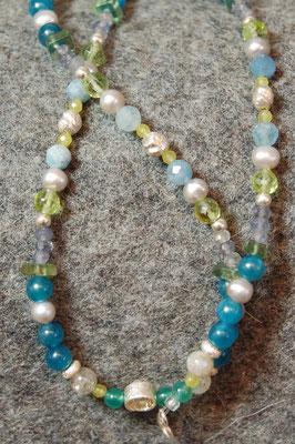 Sehr vielseitiges Stück, da verschiedene Edelsteine in unterschiedlichen Schliffen und Süßwasserzuchtperlen mit  Silberelementen miteinander harmonisch kombiniert wurden. Hauptfarben sind blau, grau und grün.