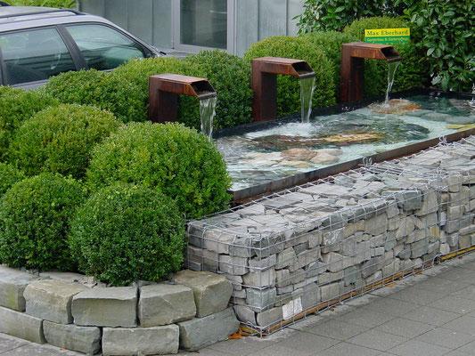 Steinkörbe und Sandsteine, dahinter Brunnen aus Stahl