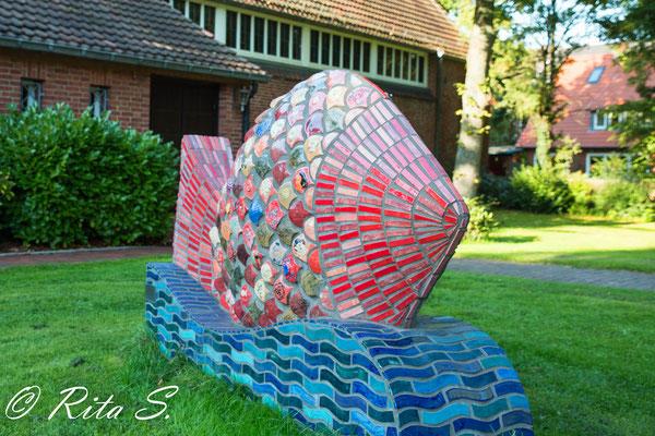 vor der Kirche ein steinerner Fisch, geschaffen in der JVA Bremen-Oslebshausen.