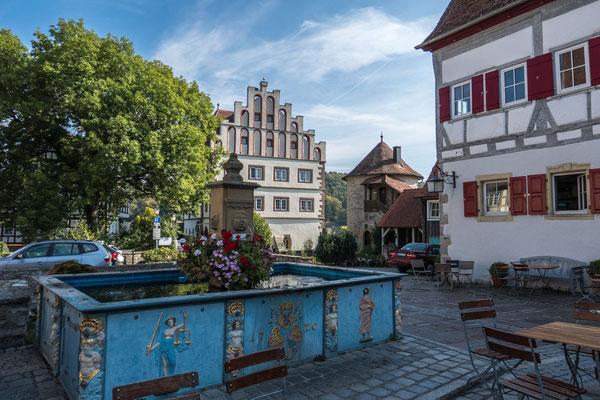 © Traudi - Der Marktbrunnen aus dem Jahr 1720 steht direkt in der Mitte des Städtles neben dem ehemaligen Feuersee. Da Vellberg in der Zeit von 1596 bis 1802 zur Reichsstadt Hall gehörte, ist auch das Wappen inmitten der Reliefbilder angebracht.,