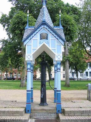 Brunnen auf dem Marktplatz. Auf der Stirnseite des Brunnenhäuschens befinden sich 4 Versinschriften, die von Klaus Groth in plattdeutscher Sprache speziell über das Wasser gedichtet wurden.