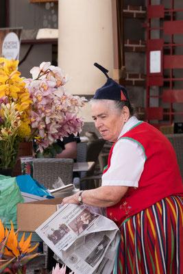 In traditionele klederdacht uitgedoste bloemenvrouwtje bij de mercado van Funchal, Madeira