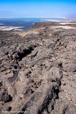 """Vue depuis le compartiment Nord du Rift vers l'Ouest - Du fond vers le premier plan : le Lac Asal, les coulées du Manda (les plus noires sont celles de l'Ardoukôba), une faille au sommet (prolongement du """"Petit Rift"""", enfin une coulée en tube."""