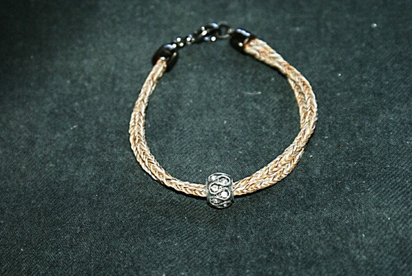 Ein zweistrangiges Armband, wo die Stränge leicht verdreht sind. Verziert mit einem Tropfenbead.