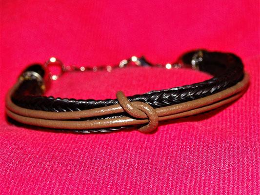 Ein zweistrangiges Armband mit zwei Lederbänder verziert. Das Armband wird mit dem Knoten zusammengehalten.