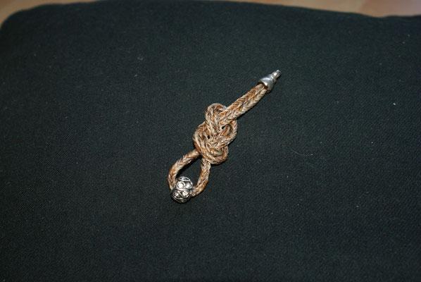 Hier wurde ein doppelter Achterknoten gelegt und eine Perle in der Mitte angebracht.
