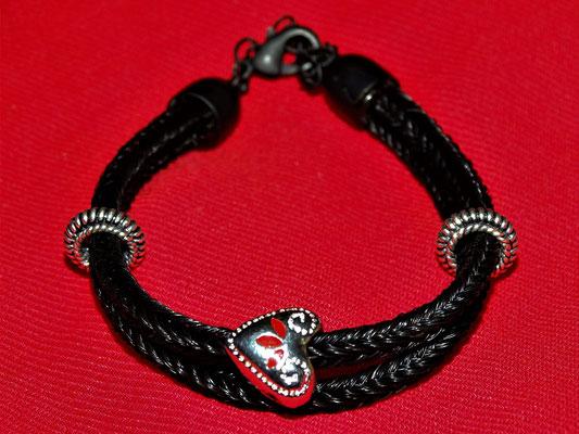 Ein Herz mit rotem Farbton verziert das schwarze, doppelstrangige Armband.