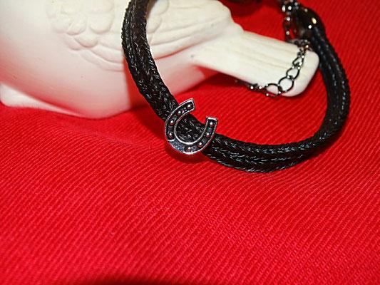 Ein schlichtes, doppelstrangiges Armband mit einem glückbringenden Hufeisen. Durch die zwei Stränge hält das Hufeisen in der Mitte des Armbandes.