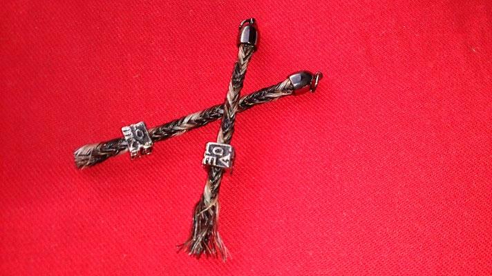 Zwei Schlüsselanhänger kombiniert aus Geflecht und losen Haaren am Ende des Geflechtes.