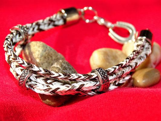 Ein dreistrangiges Armband, wo die Stränge mit silbernen Ringen zusammengehalten werden.