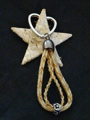 Ein Schlüsselanhänger mit zwei Strängen aus unterschiedlichen Geflechten, verbunden mit einem Bead.