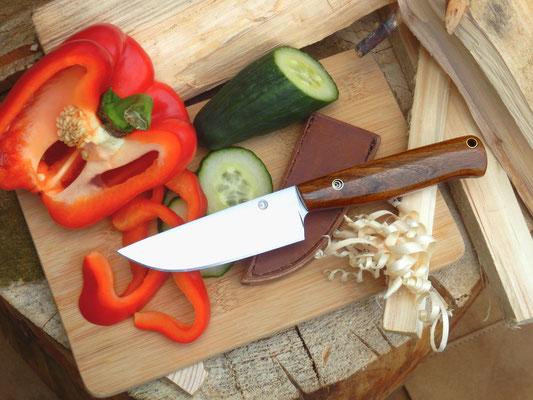 Konzipiert für die Küche, Wald und Wiese, kann dieses Messer aus Kohlenstoffstahl und mit Griff aus Nussholz mit der simplen Lederscheide einfach in den Rucksack gelegt werden und ist so überall einsetzbar.