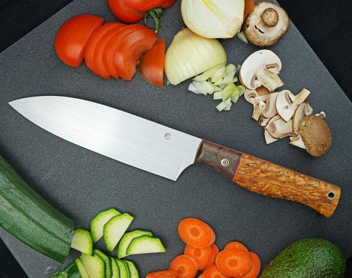 Ein Chefmesser für die Küche mit einem Griff aus stabilisiertem kaukasischem Nussholz und stabilisierter karelischer Maserbirke.