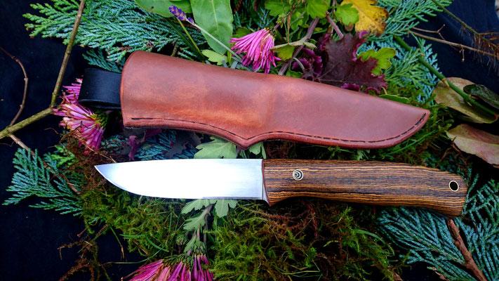 Ein kräftiges Messer für alle Eventualitäten, mit Lederscheide aus in Bienenwachs getränktem Blankleder. Stahl: Kohlenstoffstahl, Griffmaterial: südamerikanische Bocote