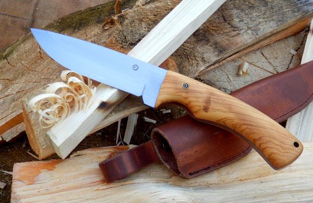 Ein Outdoor Messer aus Kohlenstoffstahl, mit einem Griff aus wildem Olivenholz und einer heißgewachsten Lederscheide.
