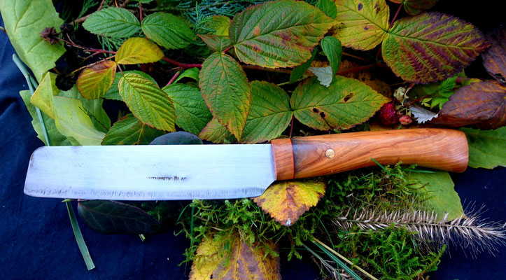 Ein großes, rustikales Küchenmesser hat einen neuen Griff aus wildem Olivenholz bekommen.
