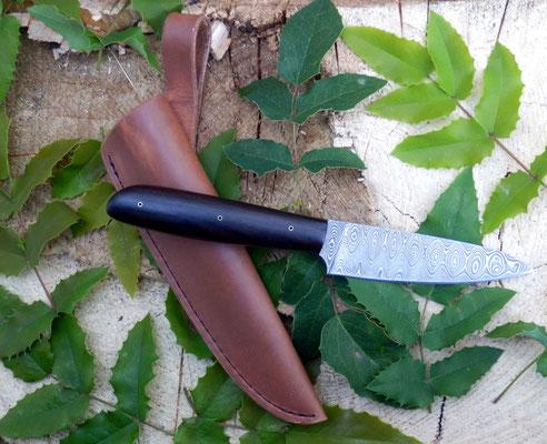 Schlankes Allzweckmesser aus wunderschönem Leiterdamast mit 192 Lagen mit dazu passender Lederscheide, Griffmaterial: Makassar-Ebenholz.